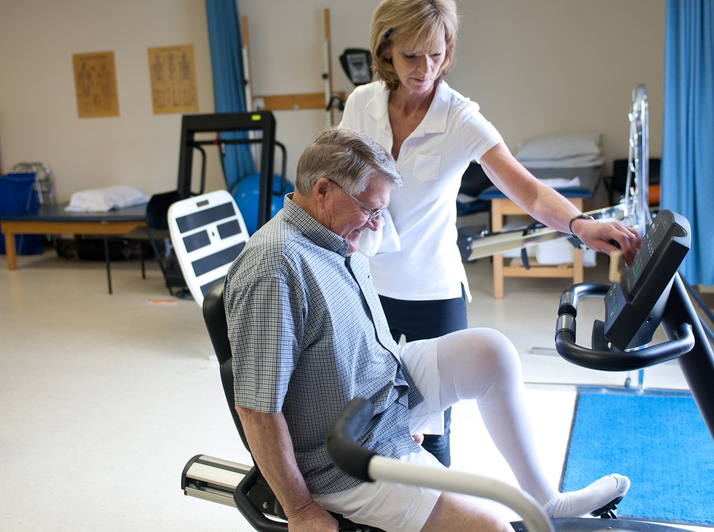 patient on a bike while therapist watches over