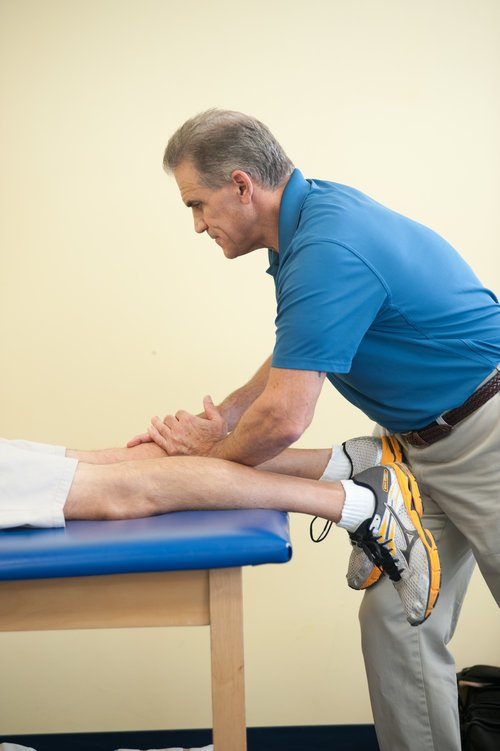 therapist massaging patients right calf