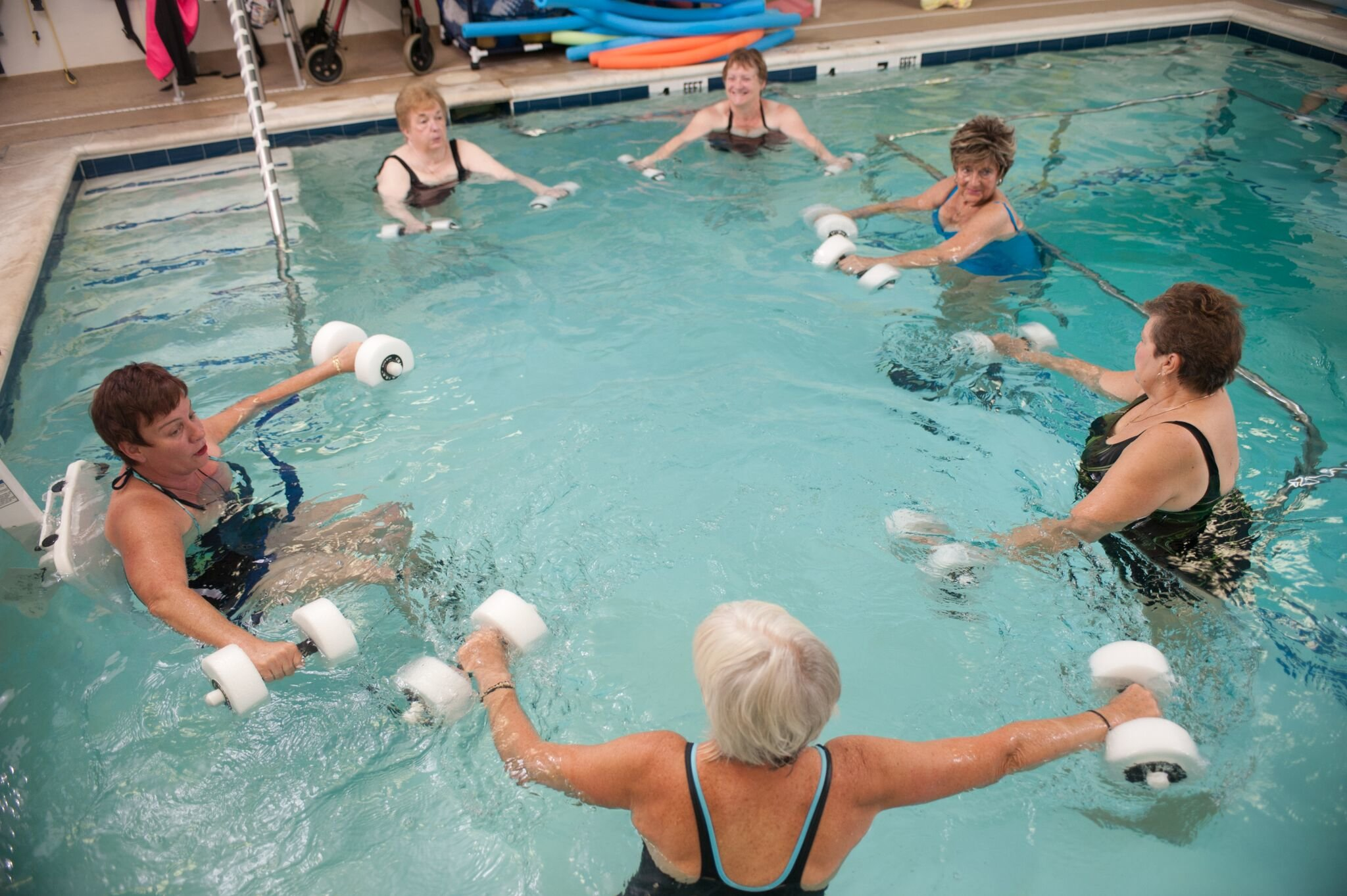 several elderly patients exercising with hand wieghts in pool