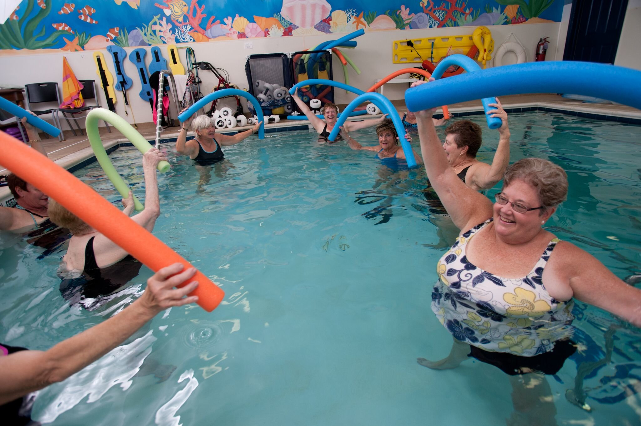several elderly patients exercising with pool noodles in pool