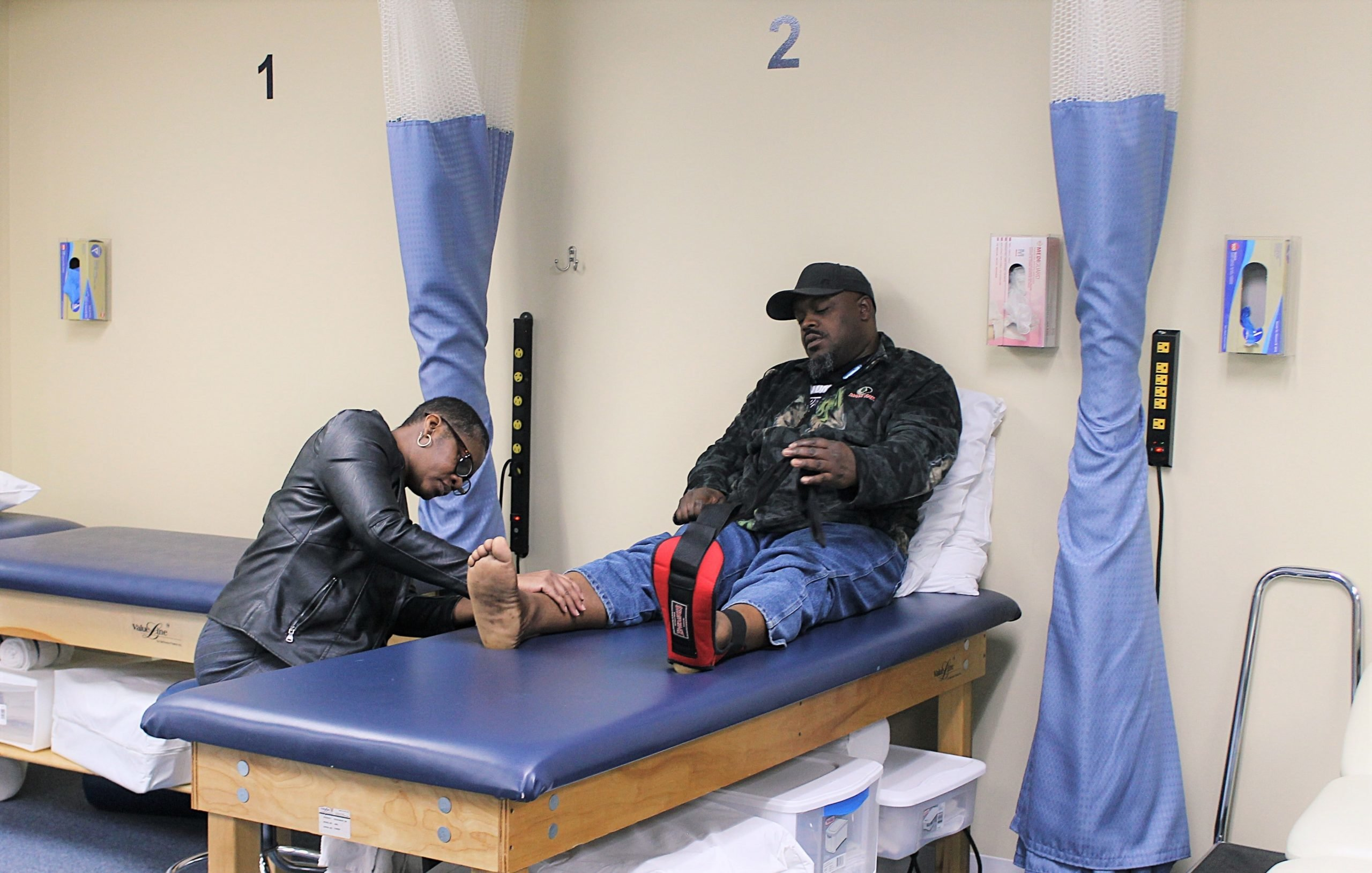 female physical therapist examining leg of patient sitting on examination table