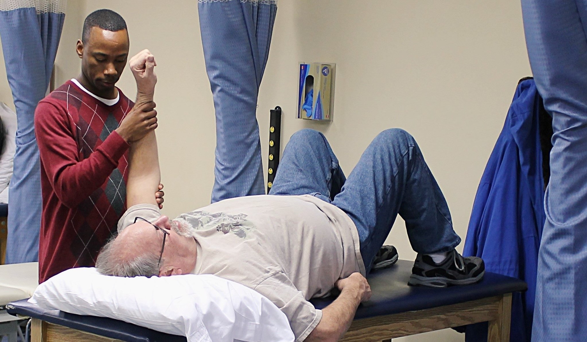 male performing physical therapy on elderly patient
